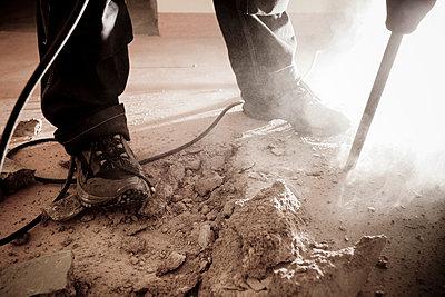 Man operating jackhammer in cellar - p1687m2284249 by Katja Kircher