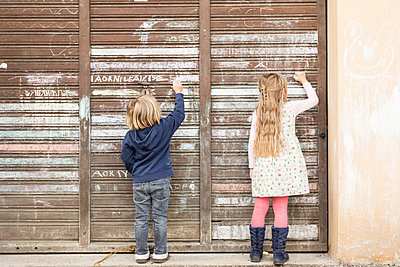 Back view of two little girls drawing on an old garage door - p300m1129909f von Stefan Rupp