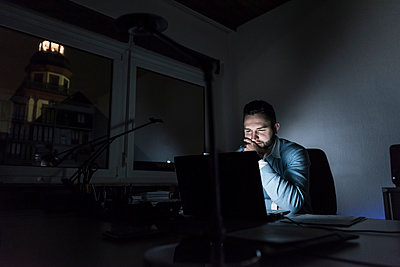 Businessman working on laptop in office at night - p300m1581593 by Uwe Umstätter
