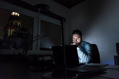 Businessman working on laptop in office at night - p300m1581593 von Uwe Umstätter