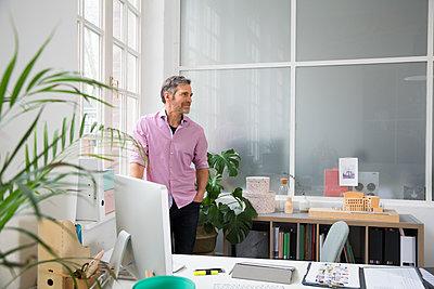 Man standing at the window in a loft office - p300m2012527 von Florian Küttler