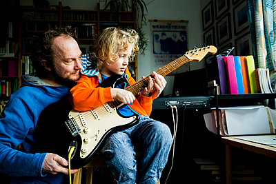 Father teaching electric guitar to blond son while sitting at home - p300m2275344 by Irina Heß