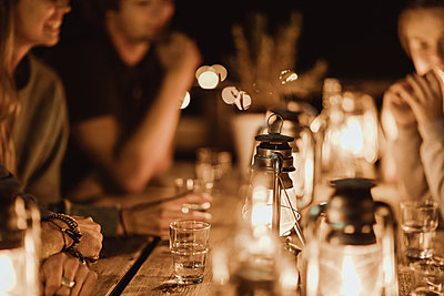 Friends sitting around illuminated table in restaurant at night - p426m2165431 by Maskot