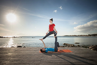 Women practising acro yoga at seaside - p429m2090625 by ROBERTO PERI