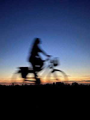 Frau auf Fahrrad in der Abendsonne, Bewegungsunschärfe - p958m2290814 von KL23