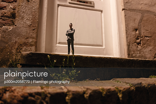 Businessman figurine standing on stairs in front of an entrance door - p300m2058770 by Flamingo photography