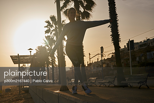 Young woman balancing on promenade at the beach at sunset - p300m2167440 by Pablo Calvo
