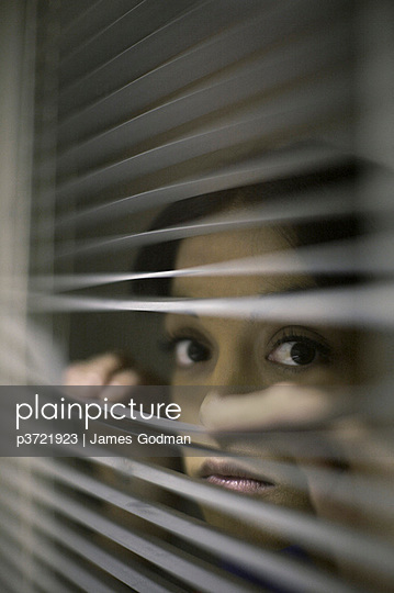 Young woman peering through blinds - p3721923 by James Godman