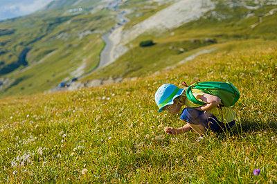 little boy crouching on alpine meadow near Tre Cime di Lavaredo - p300m885088f by Jana Mänz