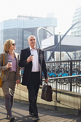 Two businesspeople walking in city - p429m803577f by Liam Norris