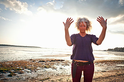 Mature woman exercising on beach - p429m943064f by Grant Squibb
