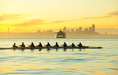 Team rowing boat in bay - p555m1478280 by Pete Saloutos