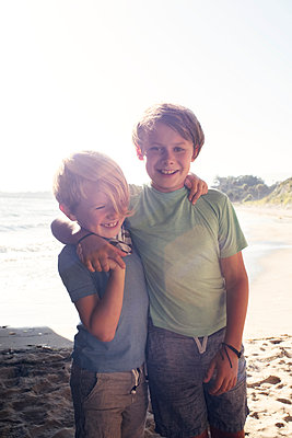 Portrait of two smiling boys, standing on beach, arm around shoulder, looking at camera, Santa Barbara, California, USA. - p924m2208566 by JFCreatives