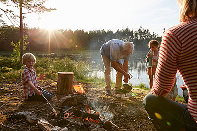 Grandparents and grandchildren at campfire at sunny lakeside in woods - p1023m1172705 by Francis Pictures
