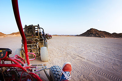 Beach buggies riding on dessert against clear sky - p1166m1037048f by Cavan Images
