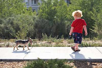 Full length of baby boy walking with puppy on footpath in park - p1166m2067854 by Cavan Images