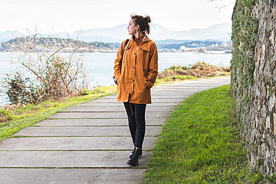 Young woman walking alone along coastal promenade of Bay of Biscay - p300m2266341 by Josu Acosta