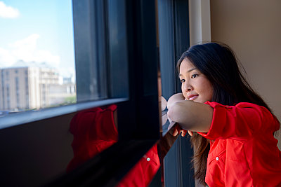 Thoughtful young woman looking through window - p300m2273765 by Buero Monaco