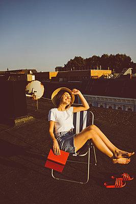 Junge Frau sitzt entspannt mit Buch auf Hausdach - p432m2260317 von mia takahara