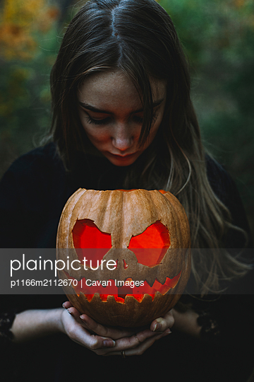 Young woman holding illuminated jack o' lantern while standing in forest during Halloween - p1166m2112670 by Cavan Images