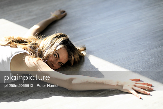 Young woman lying on floor - p1258m2086613 by Peter Hamel