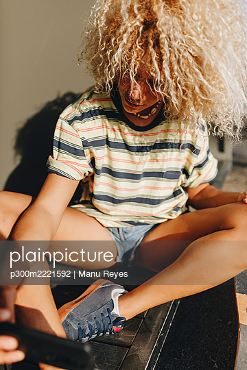 Blond Afro woman taking selfie through smart phone on sunny day - p300m2221592 by Manu Reyes