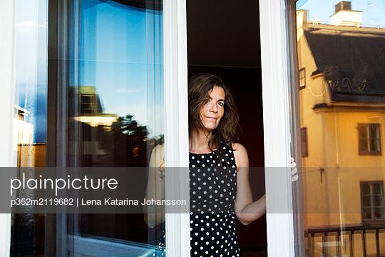 Woman opening door - p352m2119682 by Lena Katarina Johansson