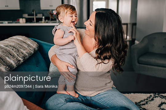 Mother playing with baby daughter on sofa - p924m2097344 by Sara Monika