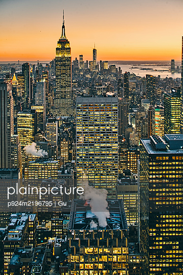 View of Manhattan skyline with illuminated skyscrapers at sunset, New York City - p924m2196795 by Gu