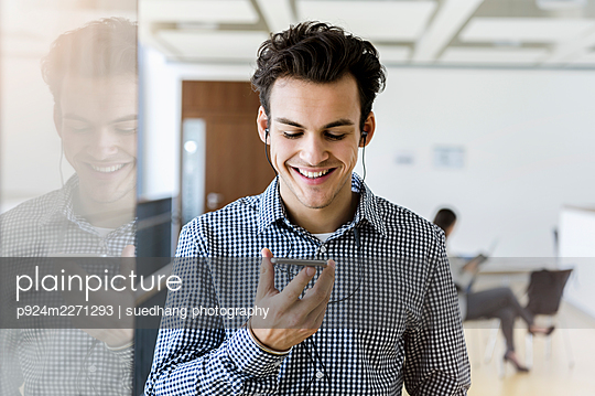 Germany, Bavaria, Munich, Smiling young man using smart phone and headphones - p924m2271293 by suedhang photography