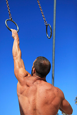Man with gymnastic rings - p0452808 by Jasmin Sander