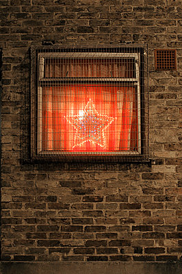Illuminated Christmas star in window behind bared security cage - p1072m829287 by Neville Mountford-Hoare