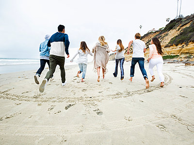 A group of young men and women running on a beach, having fun. - p1100m1038929 by Mint Images