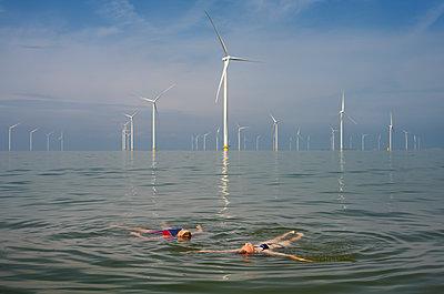 Zwei Frauen im Meer im Hintergrund ein Windpark - p1132m2291579 von Mischa Keijser