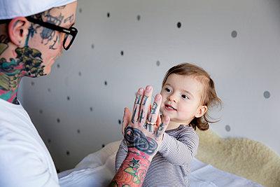 Tätowierter Vater mit Kind im Kinderzimmer - p1212m1108587 von harry + lidy