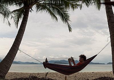 Man in hammock reading book - p1324m1441286 by michaelhopf