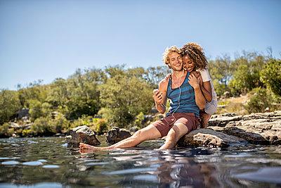 Junges Paar entspannt sich am Flussufer - p1355m1574205 von Tomasrodriguez