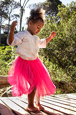 Little girl in pink tulle skirt makes dance steps - p1640m2246819 by Holly & John