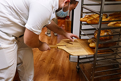 Male baker keeping bread loaf on rack with pizza peel in commercial kitchen at bakery - p300m2243642 by Jose Luis CARRASCOSA