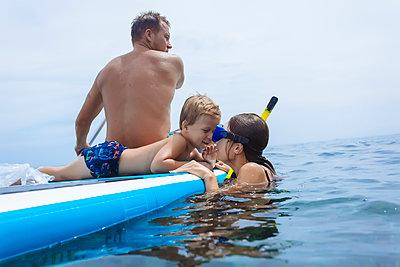 Family on sup surfboard in ocean,Bali,Indonesia - p343m1578167 by Konstantin Trubavin