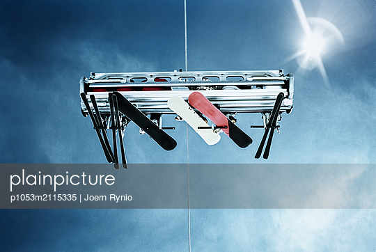 Looking up at skiers riding chairlift - p1053m2115335 by Joern Rynio