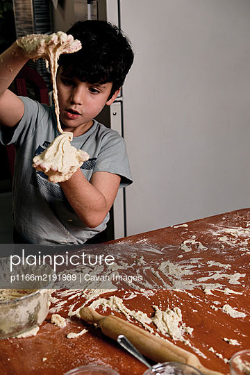 child preparing pizza dough to make at home - p1166m2191989 by Cavan Images