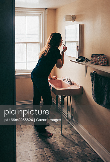 Woman leaning against pink sink in old bathroom to apply make up. - p1166m2255824 by Cavan Images