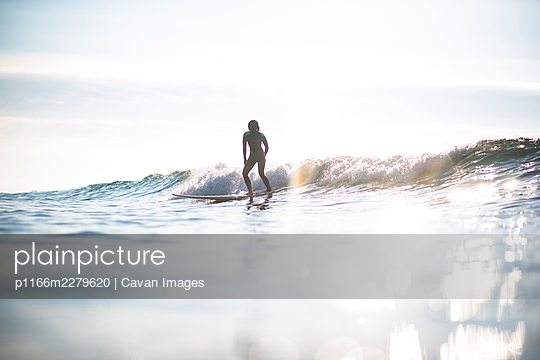 Asian Woman surfing waves during sunrise summer surf session - p1166m2279620 by Cavan Images
