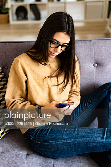 Young woman wearing eyeglasses using mobile phone while sitting on sofa at home - p300m2251525 by Giorgio Fochesato