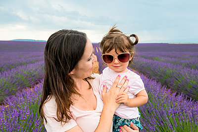 Happy mother and daughter walking among lavender fields in the summer - p1166m2136657 by Cavan Images