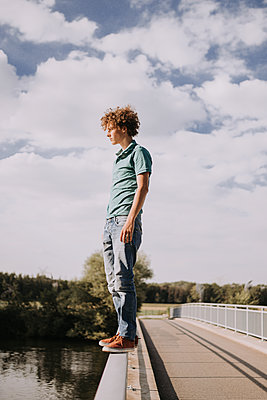 Young man on bridge railing, portrait - p1267m2259690 by Jörg Meier