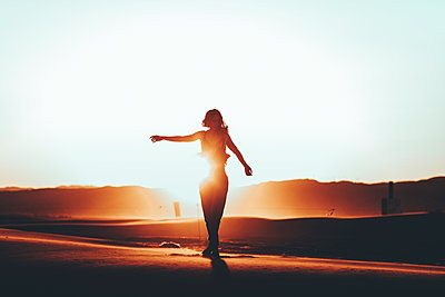 Silhouette of woman standing in desert landscape at sunset - p300m2005449 by Oriol Castelló Arroyo