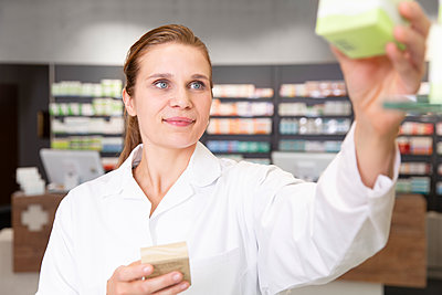 Smiling female pharmacist with medicine in store - p300m2251814 by Florian Küttler