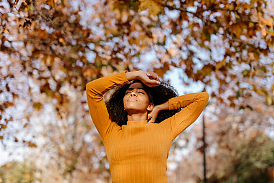 Young Afro woman with eyes closed in park on autumn - p300m2268157 by Tania Cervián